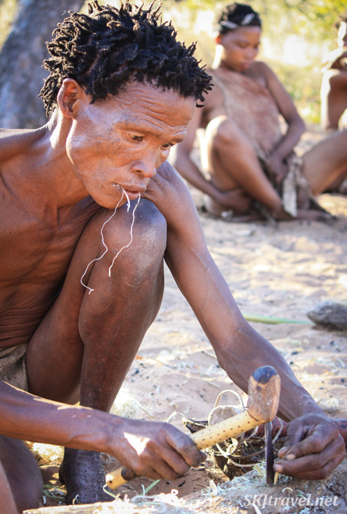 San man making an arrow at the Ju/'Hoansi-San Living Museum near Grashoek, Namibia.