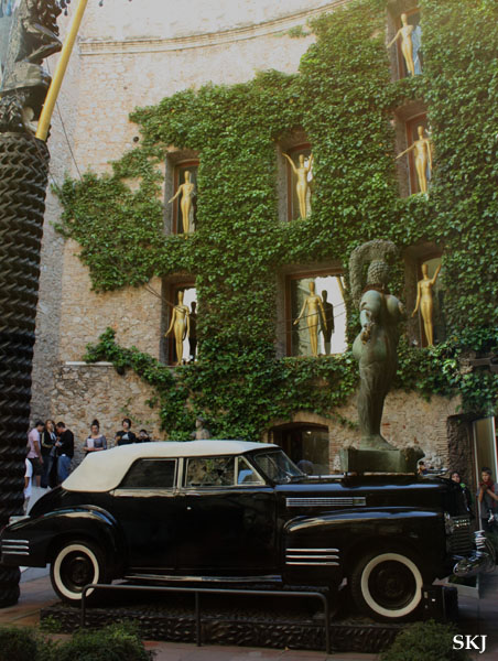 """Car-naval"" - Outdoor courtyard with statues in window niches and ivy on the walls and an old car at Dali museum in Figueres Spain. photo by Shara Johnson"