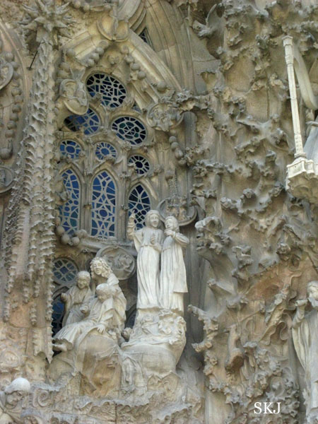 Exterior of Sagrada Familia outside stained glass window with a scene of stone statues outside the window. photo by Shara Johnson