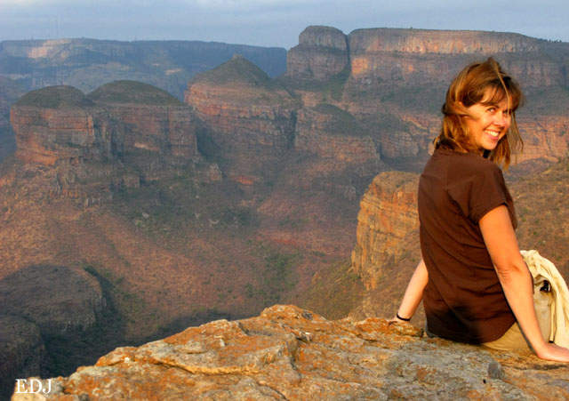 girl sitting looking over a large red canyon