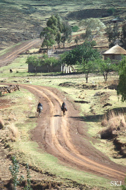 two men on horseback riding down dirt road in mountains. Lesotho.