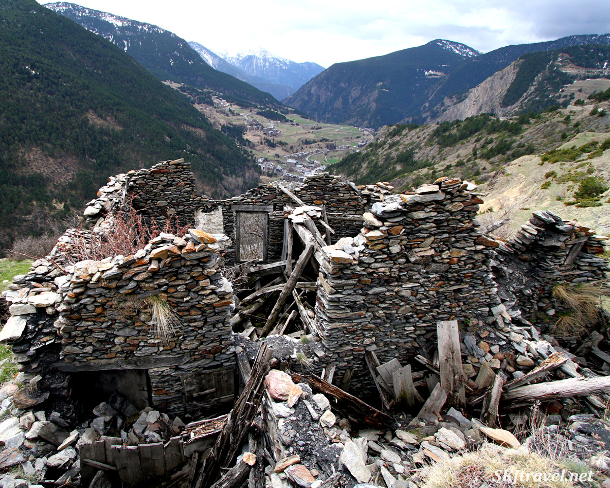 Small farmstead ruins on a hillside overlooking a village in the valley. Andorra.