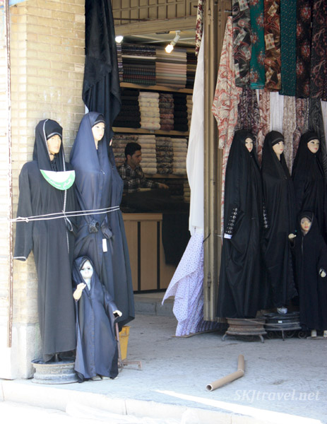 Women and children mannequins wearing black chadors. On a sidewalk outside the Friday Mosque in Isfahan, Iran.