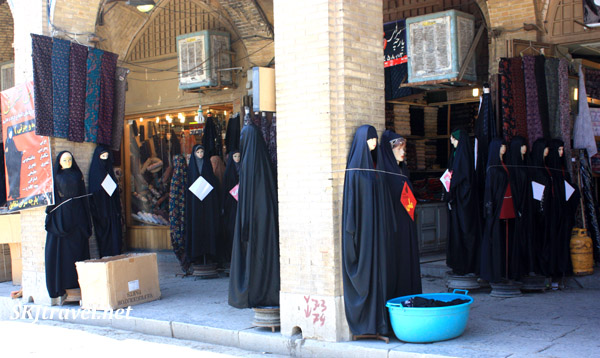 Rows of mannequins wearing black chadors, on a sidewalk in Isfahan, Iran. Outside the Friday Mosque.