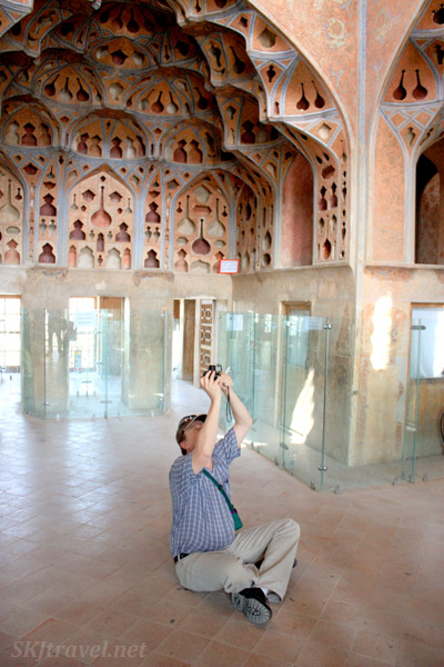 Erik sitting on the floor to snag a photo of the carved wooden ceiling, Ali Qapu, Isfahan, Iran.