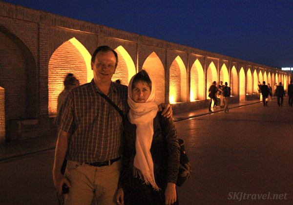 Throngs of people, including Erik and Shara, stroll across the pedestrian bridge lit up at night over the dry Zayandehrood River. Isfahan, Iran.