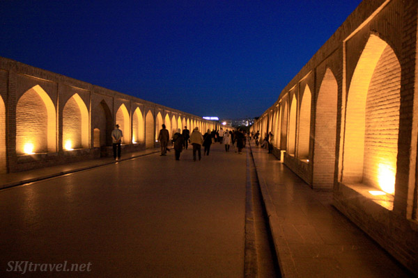 Throngs of people stroll across the pedestrian bridge lit up at night over the dry Zayandehrood River. Isfahan, Iran.