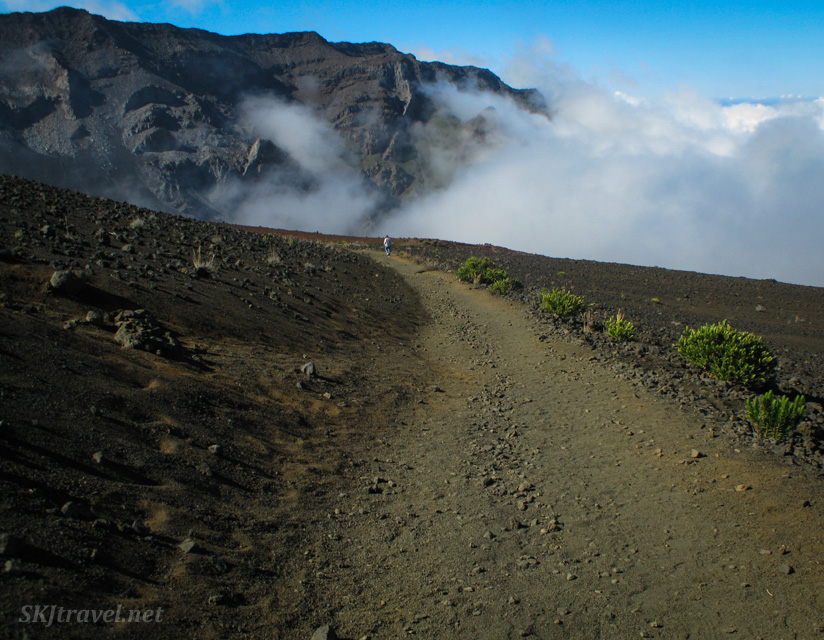 Erik walks toward a cloud bank inside the caldera of Haleakala volcano, Maui, Hawaii.