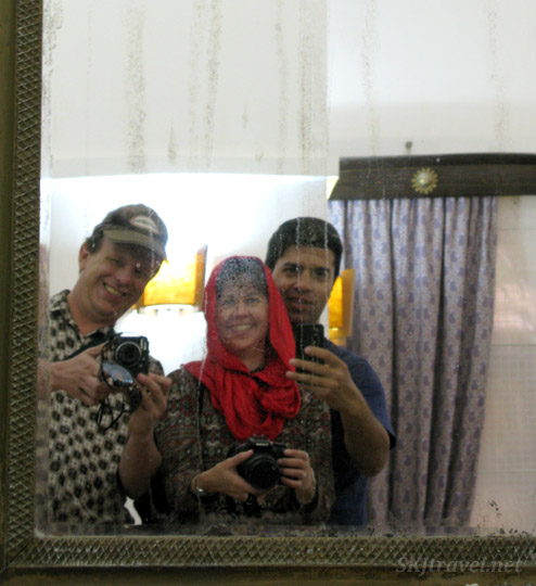 Three people all taking a selfie of the three of them in a mirror. Hotel in Yazd, Iran.