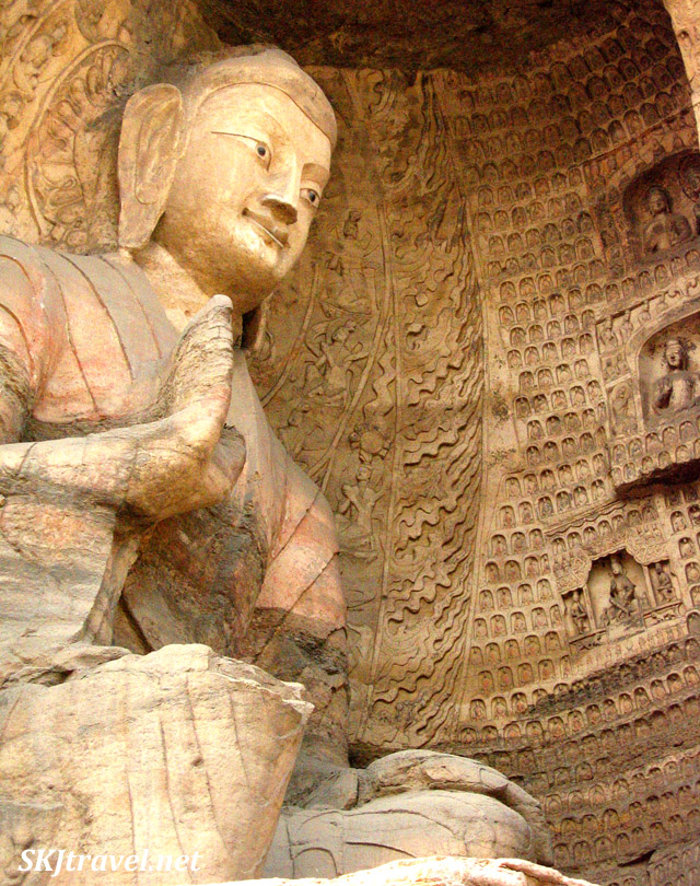 large buddha carved into cliffside with small statues surrounding