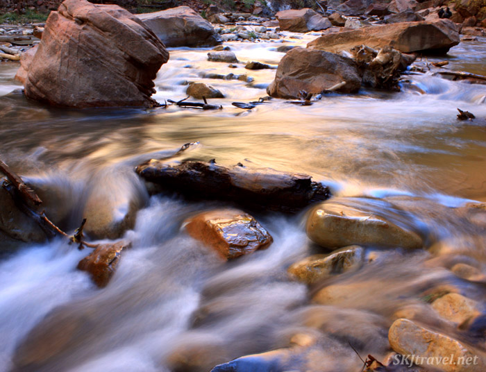 shallow river water swirling around rocks.