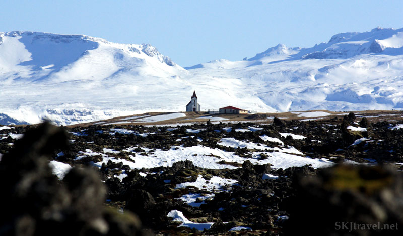 Small church behind lava field with white mountains