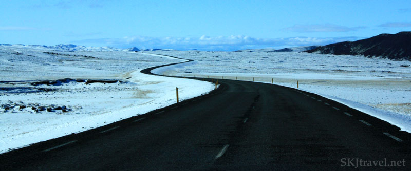 snaking black road in snowy field