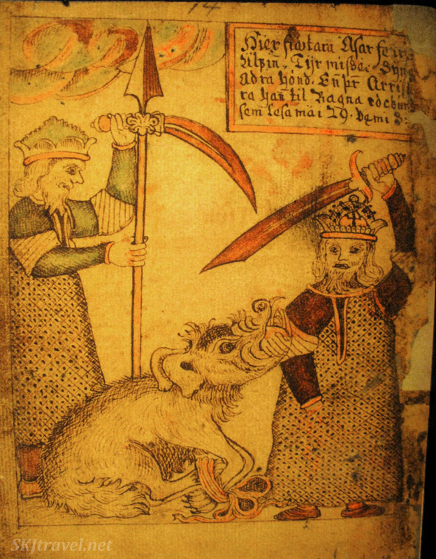 About to kill the attacking beast. Page from a medieval Icelandic saga manuscript, in the Culture House, Reykjavik, Iceland.
