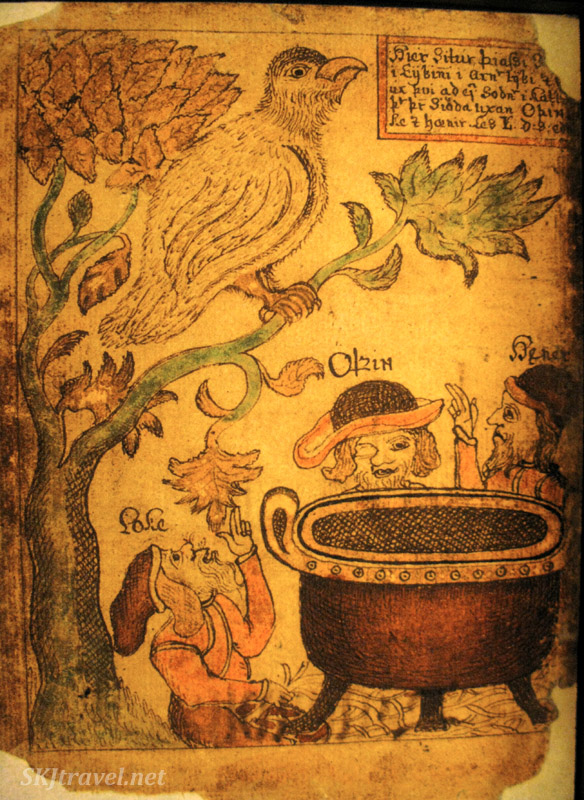 Men sitting around a cauldron ... wonder what's in it? Page from a medieval Icelandic saga manuscript, in the Culture House, Reykjavik, Iceland.