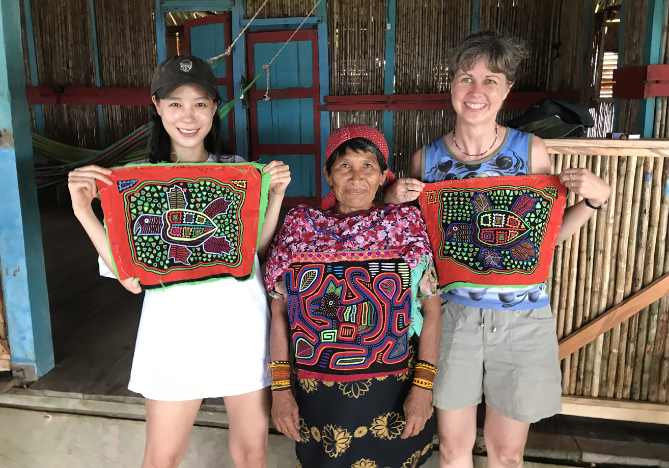 Me and Yoon holding the turtle design molas we bought, with the woman who made them. Armila, Guna Yala, Panama.