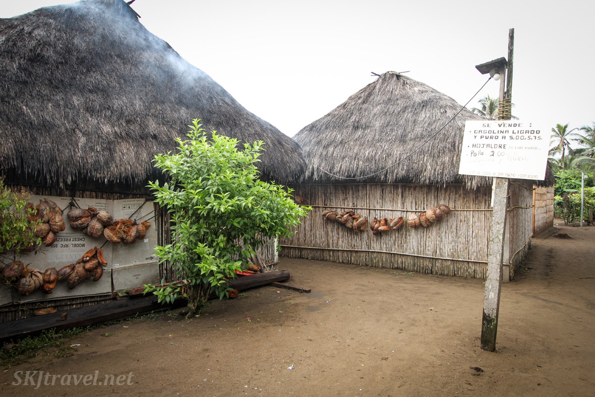 Street corner in Armila village, Guna Yala, Panama. Two large huts, smoke seeping out of the thatched roof.