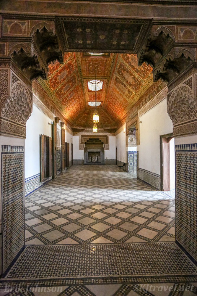 Long room in Bahia Palace with elaborately painted ceiling and skylights. Viewed through an archway. Bahia Palace, Marrakech, Morocco. UNESCO world heritage.