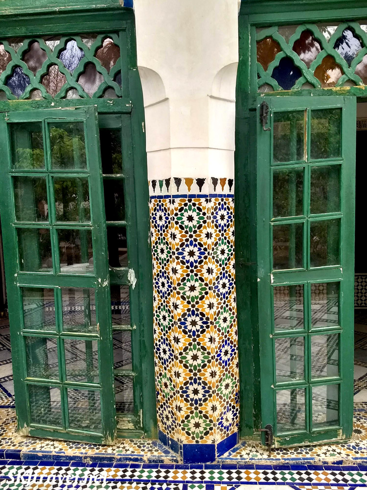 Green glass panel doors surrounding tiled pillar. Bahia Palace, Marrakech, Morocco. UNESCO World Heritage.