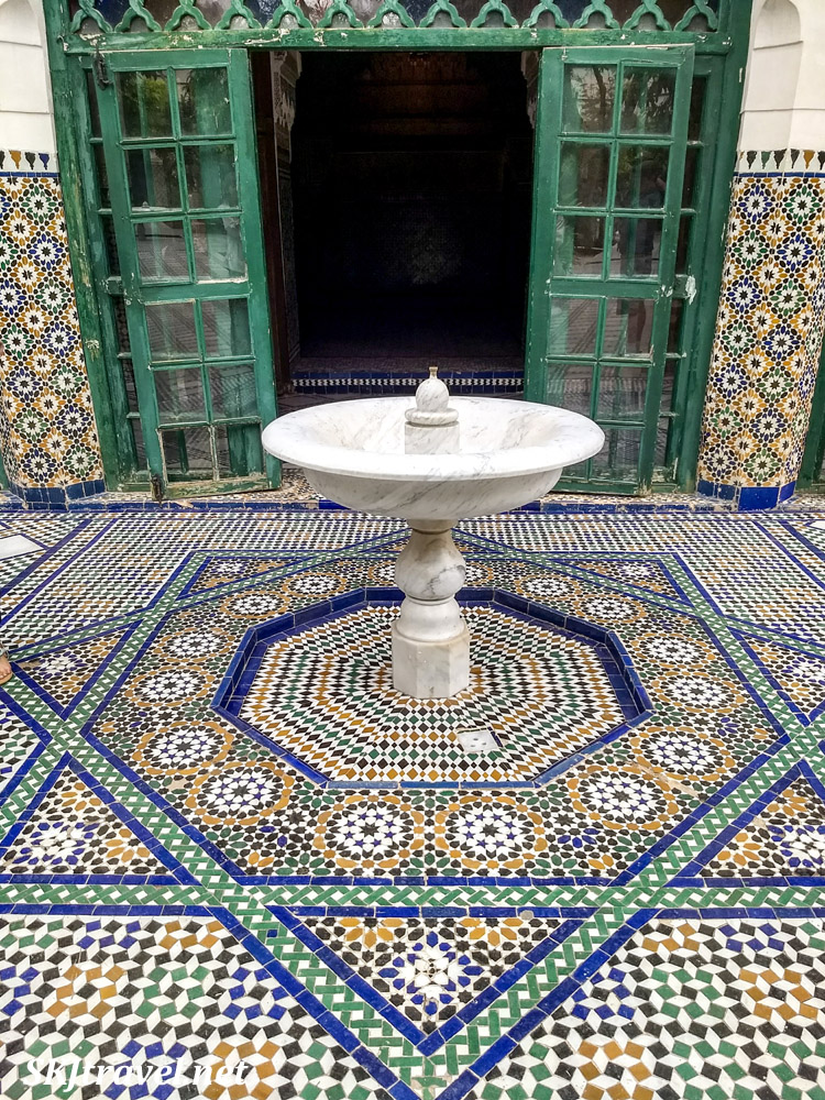 White marble fountain and detailed tile floor. Courtyard in Bahia Palace, Marrakech, Morocco. UNESCO World Heritage.
