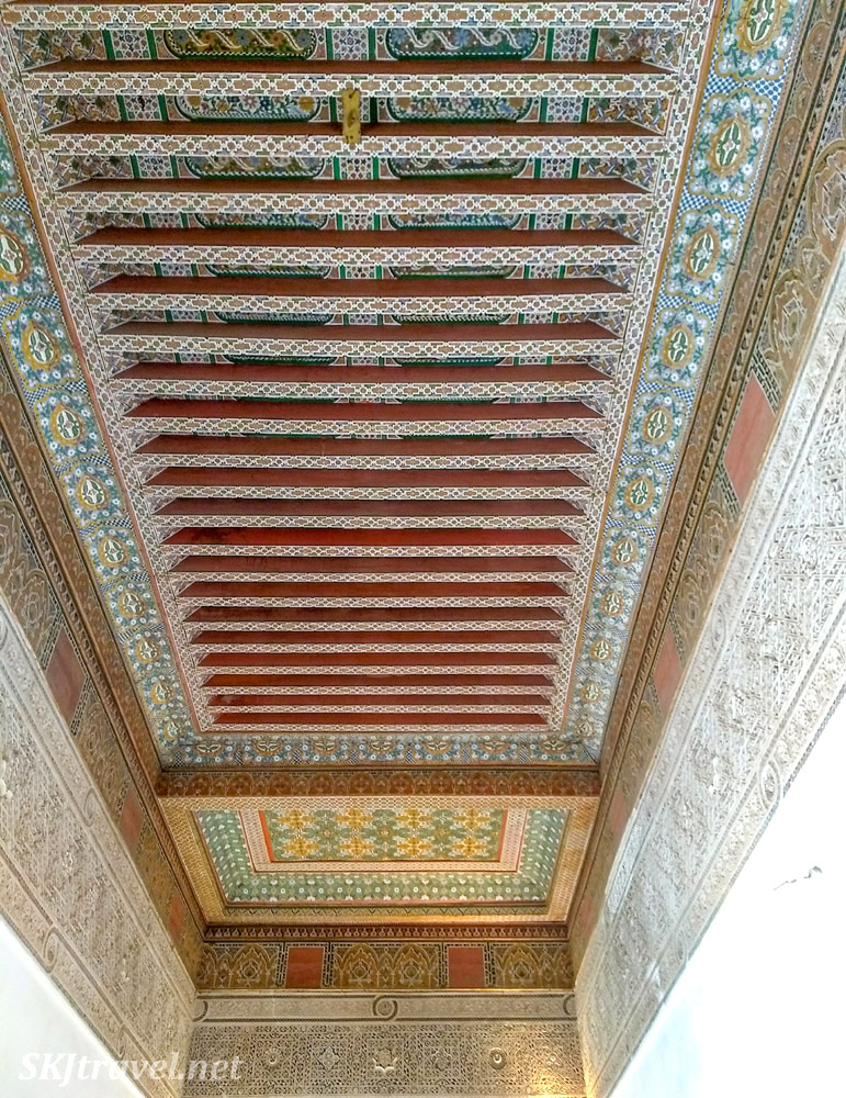 Cedarwood painted ceiling with detailed Moroccan carved stucco beneath. Bahia Palace, Marrakech, Morocco. UNESCO World Heritage.