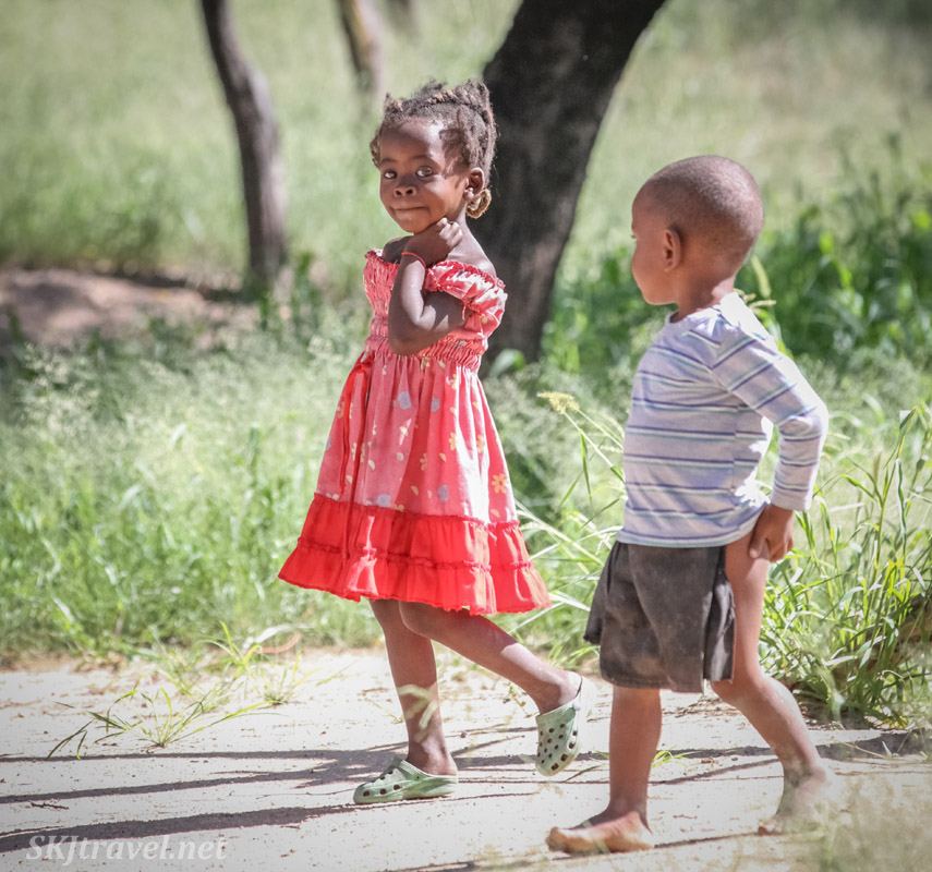 Little girl and boy walking down a road in Okahandja, Namibia.