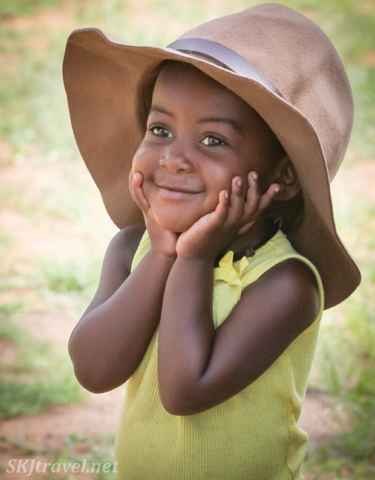 Little Himba girl in yellow and a floppy hat. Kunene region of Kaokoland, Namibia.