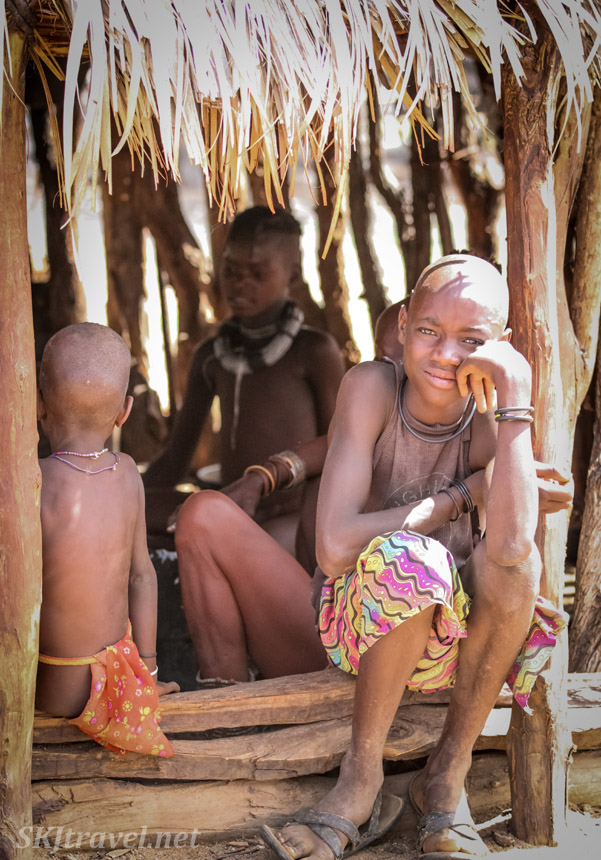 Boy sitting in the doorway of a traditional Himba hut, Kunene region of Kaokoland, Namibia.