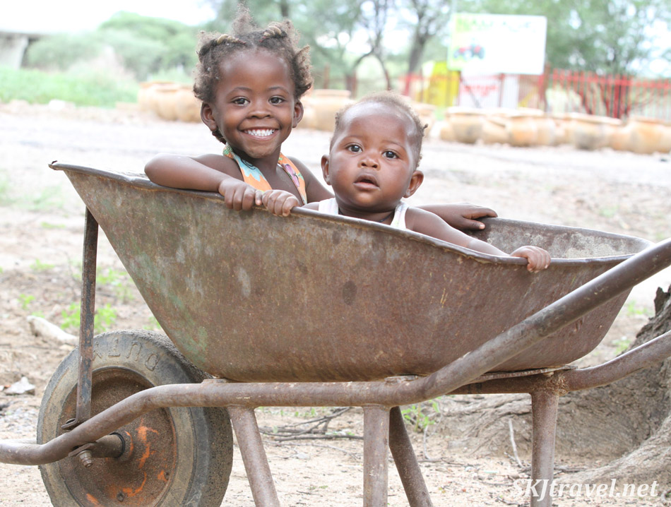 Two children in a wheelbarrow, Okahandja wood crafters market, Namibia.