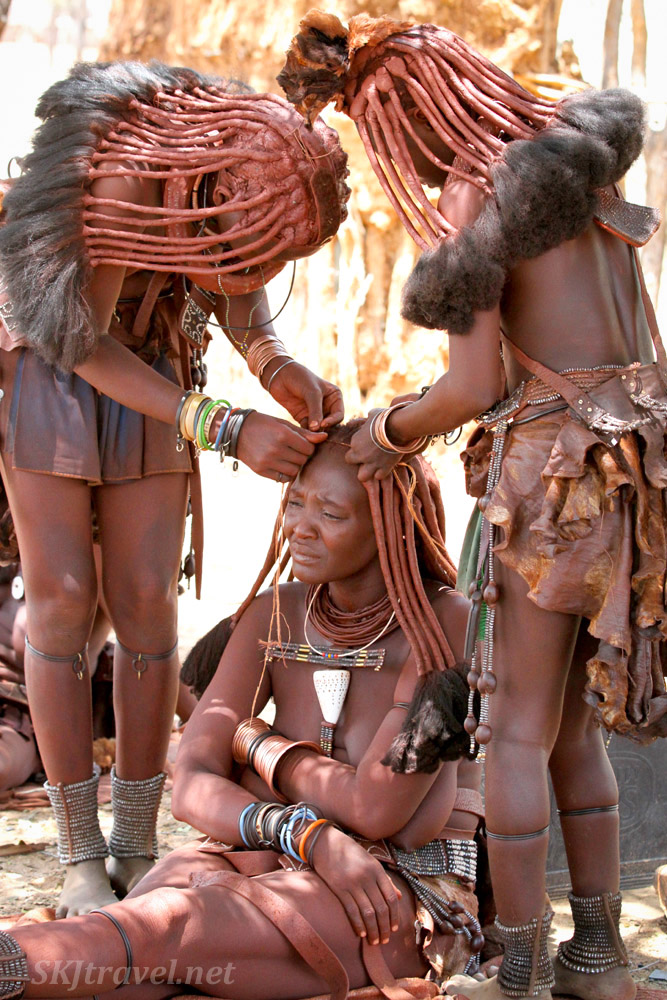 Himba women perfecting a hairstyle. Namibia.