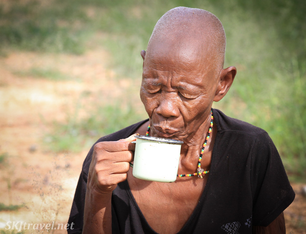 Ndjinaa drinks a cup of water. near Epupa Falls, Namibia.