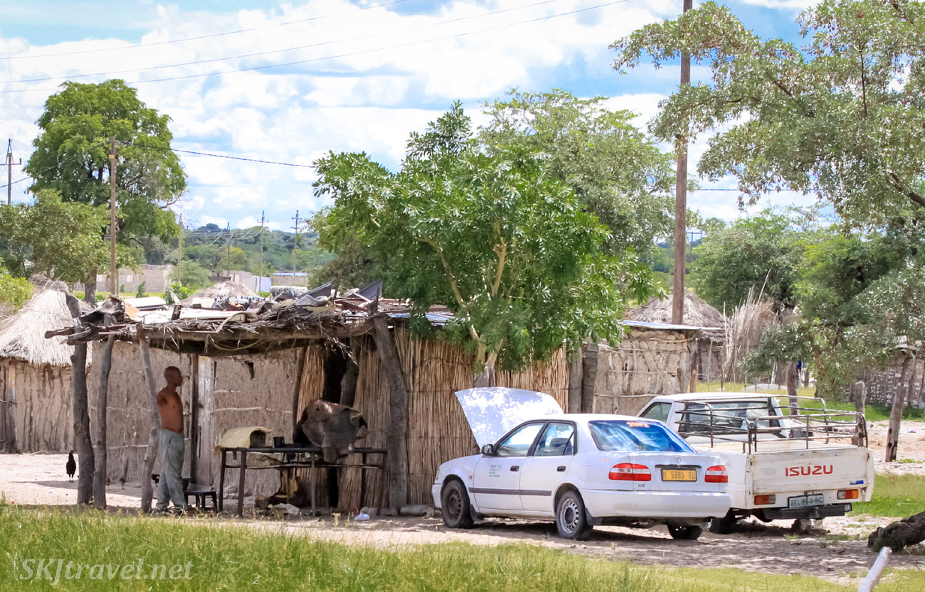Cars parked outside mud and stick huts, northern Namibia.