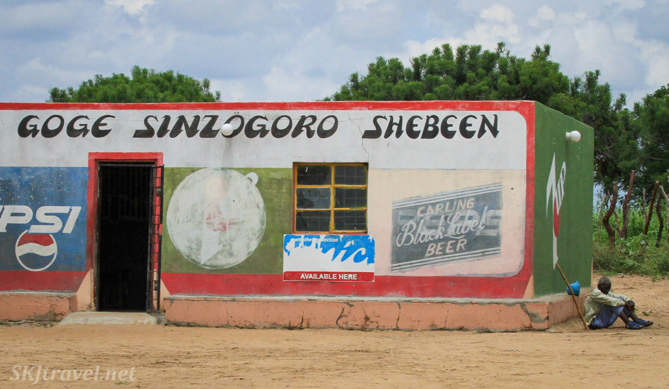 Man sitting beside a roadside shebeen, northern Namibia.