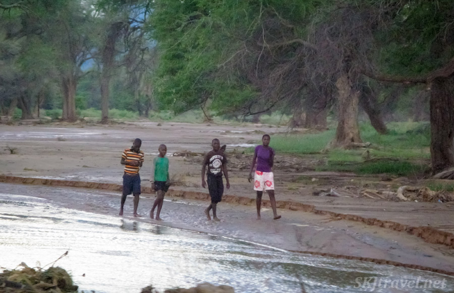 Kids walking in a river bed in the rain, northern Namibia.