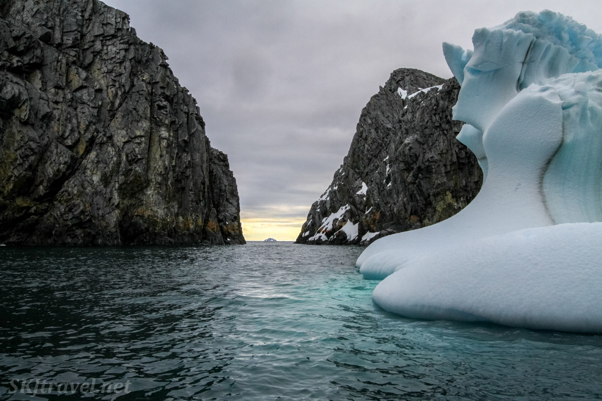 Passage through the rocks at Spert Island, Antarctica, pastel colors in the sky, giant iceberg and green waters.