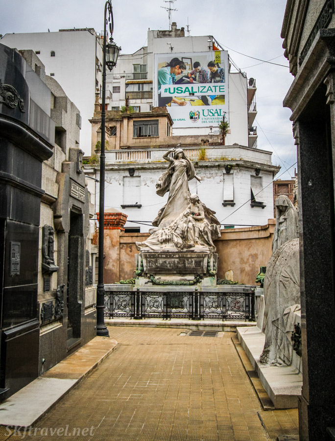 Stone statue in Recoleta Cemetery with modern high-rise building behind. Buenos Aires, Argentina.