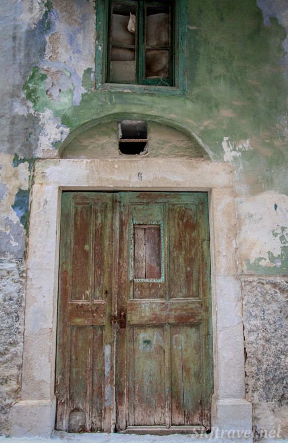 medieval mastic village of Pyrgi, Chios Island, Greece. Faded green door.
