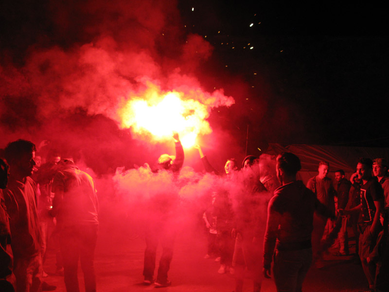 Men dancing with flares at a wedding celebration in Souda refugee camp, Chios Island, Greece.