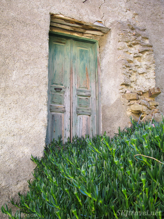 Abandoned building with faded paint of a once colorful door, Volissos, Chios Island, Greece.