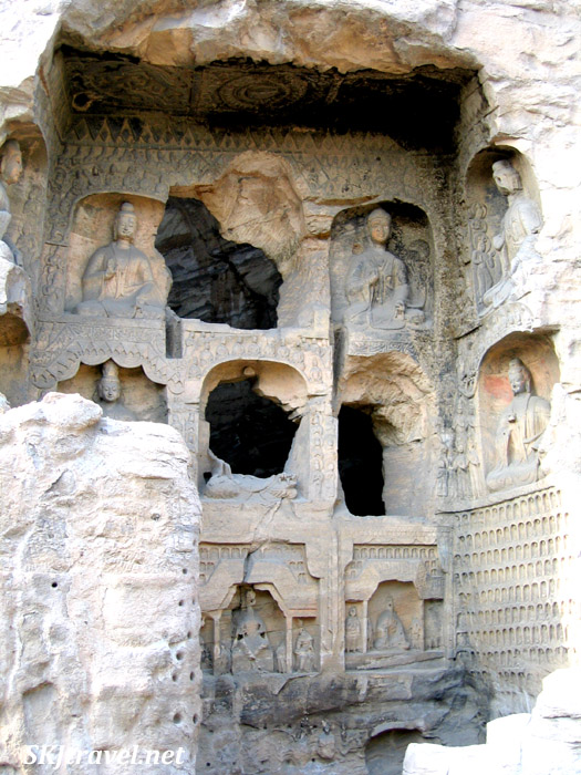 caves dug into cliff side with statues carved at entrance