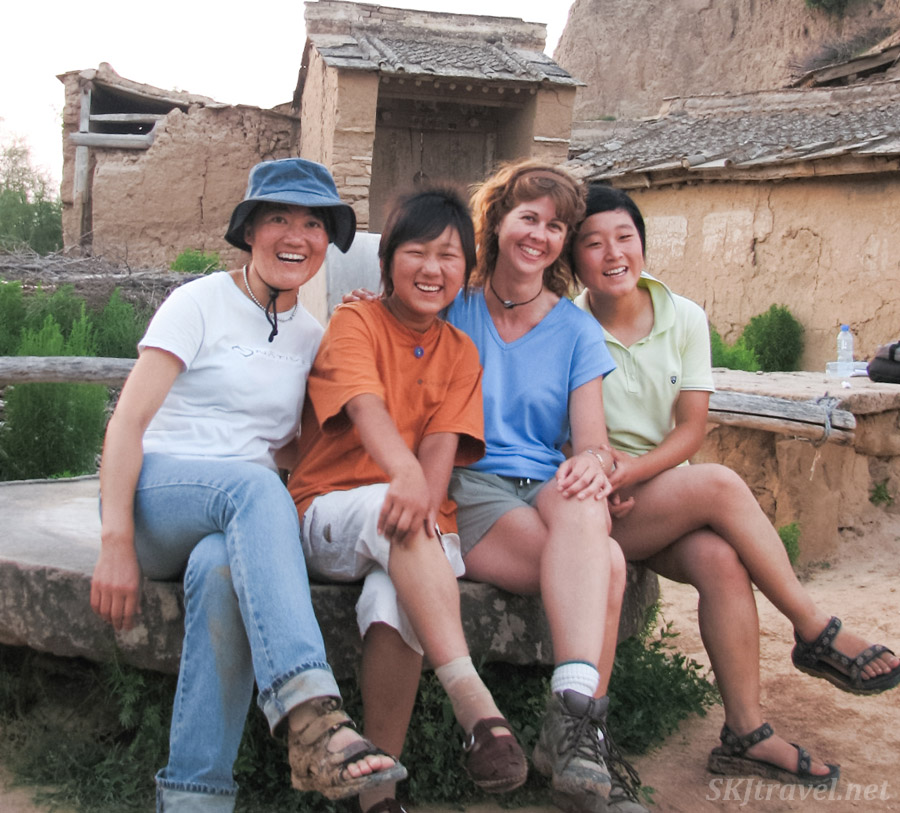 My three young friends and I sitting on a stone grinding mill in the Chinese peasant village of Dang Jia Shan, Shaanxi Province, China.