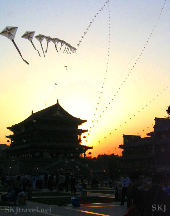 Long trails of kites being flown in the evening in the central square of Xian, China.