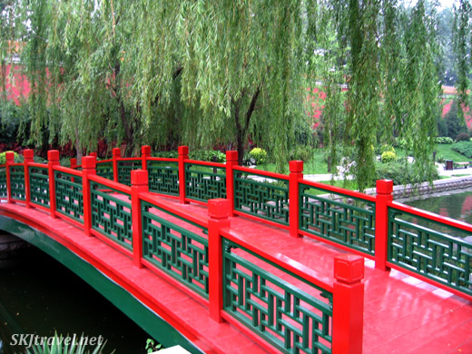 Bright red bridge over a small canal in a pretty park near Tianenmen Square. Beijing.