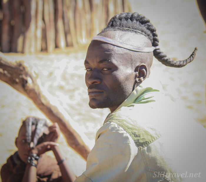 Traditional hairstyle of a young Himba man, inside his traditional kraal, Kaokoland, Namibia.