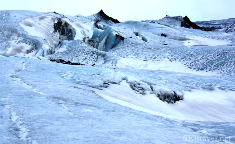 Glacier landscape, blue snow and ice, black volcanic rock and ash, Iceland. Photo by Shara Johnson