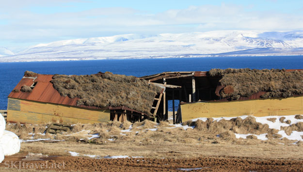 Dilapidated rectangular farm building along the coast with deep blue ocean and shite mountain backdrop in Iceland. Photo by Shara Johnson