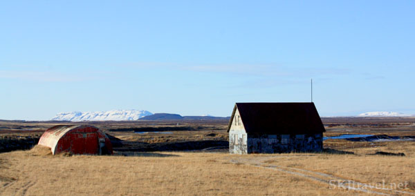 Red half-barrel farm building and rectangular structure in a brown field with snowy mountains, Iceland. Photo by Shara Johnson