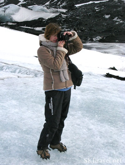 Standing on a glacier with crampons snapping a photograph in Iceland.